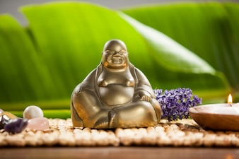 Laughing buddha figurine, lit candle and pebbles stone