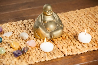 Laughing buddha figurine, pebbles stone and lit candles