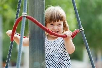 Laughing girl climbing at ropes