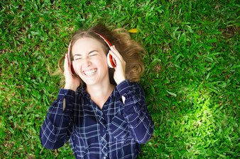 Laughing Girl Enjoying Listening to Music on Grass