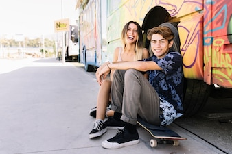 Laughing skater couple leaning against bus