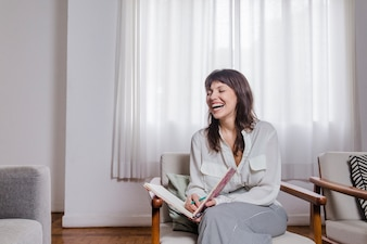 Laughing woman on chair with book