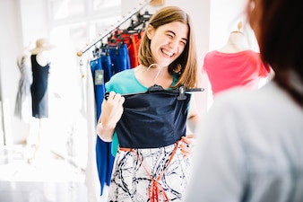 Laughing woman showing dress to her friend