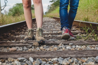 Leg view of couple on train tracks