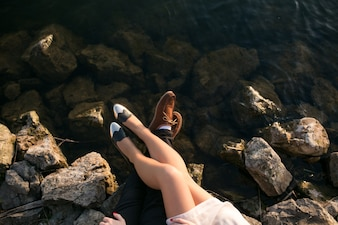 Legs of a couple on the rocks beside the sea