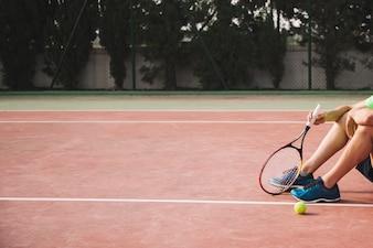 Legs of sitting tennis player