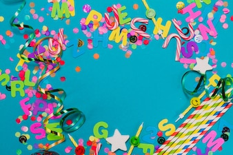 Letters, confetti and serpentine on a blue table