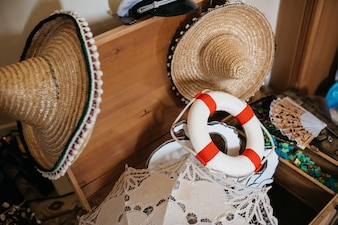 Life buoy ring lies in the wooden chest among hay Spanish hats