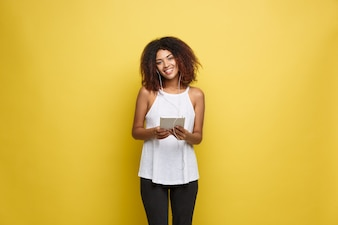 Lifestyle Concept - Portrait of beautiful African American woman joyful listening to music on tablet. Yellow pastel studio background. Copy Space.