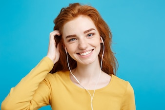Lifestyle concept - Portrait of cheerful happy ginger red hair girl enjoy listening to music with headphones joyful smiling to camera. Isolated on Blue Pastel Background. Copy space.