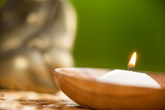 Lit candle in wooden bowl