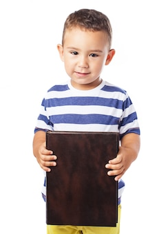 Little boy holding a closed book