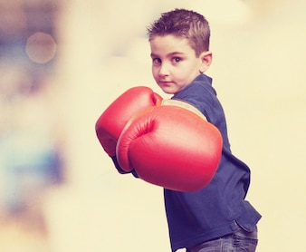 Little boy playing with boxing gloves