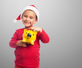 Little boy showing his yellow piggybank
