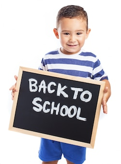 Little boy smiling with a blackboard with the message  back to school