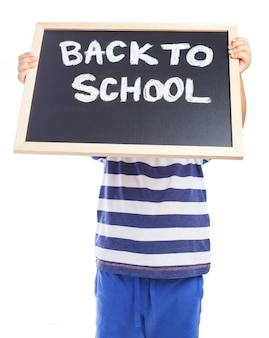 Little boy with a blackboard with the message  back to school  covering his face