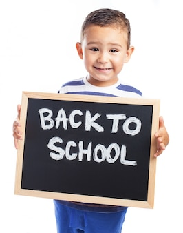 Little boy with a blackboard with the message  back to school