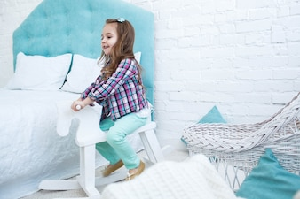 Little child rides white wooden horse in blue room