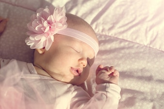 Little cute baby girl lies and sleeps in her bed, holding it hand on mouth. Beautiful sunlight. Horizontal.