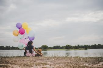 テディベアの小さなかわいい女の子が外側の長い緑の草の上に座っています。カラフルな風船を手に持っている少女。