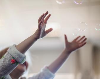 小さな女の子は、石鹸の泡をキャッチ