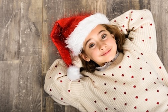 Little girl dressed as a santa claus lying on her back