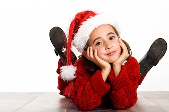 Little girl dressed as santa claus lying on the floor with hands on face
