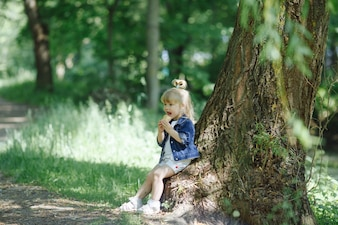 Little girl eating an ice cream leaning on a tree