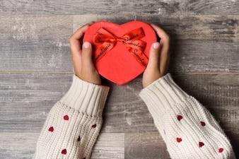 Little girl hands holding heart-shaped gift box