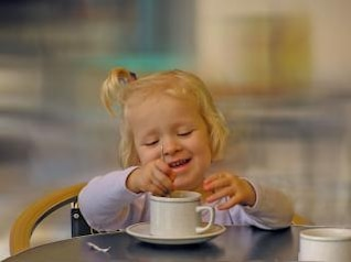 Little girl having fun with a cup