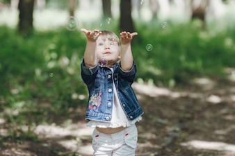Маленькая девочка с удовольствием с мыльными пузырями в парке
