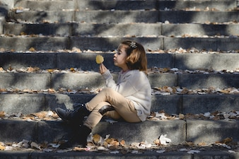 Little girl holding a leaf sitting on the stairs