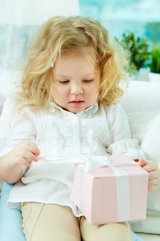 Little girl holding pink present