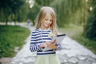 Little girl in a park playing with a tablet