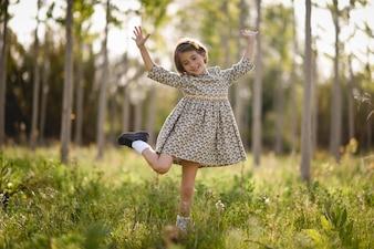 Маленькая девочка в поле природы, ношение красивое платье