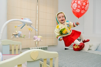 Little girl jumping on the bed with a balloon