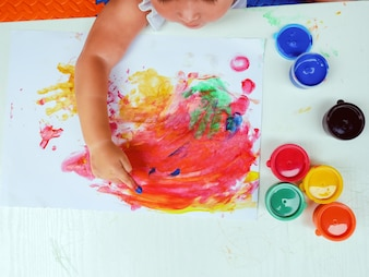 Little girl painting by finger hand paint color