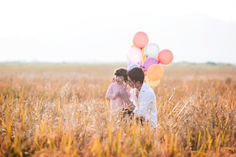 Little girl playing with balloons on wheat field