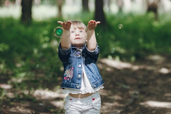 Little girl playing with soap bubbles outdoors