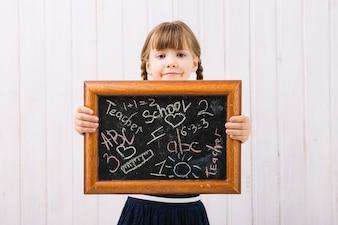 Little girl showing blackboard with chalk paintings
