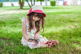 Little girl sitting on the grass looking at a mobile with headphones