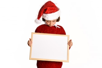 Little girl smiling with a santa hat looking at a white board