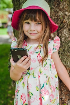 Little girl smiling with a smart phone in hand