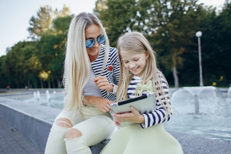 Little girl smiling with a tablet in hands