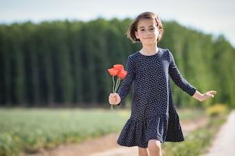 美しいドレスを着て自然のフィールドで歩いている少女