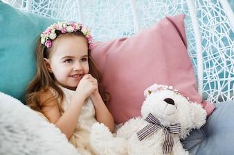 Little girl with flower wreath on her dark blonde hair holds toy white bear