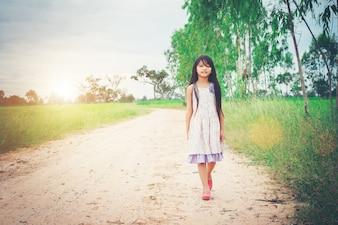 Little girl with long hair wearing dress is walking away from yo
