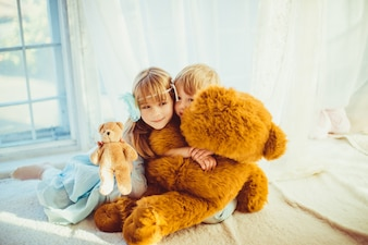 Little girls playing with a giant teddy bear