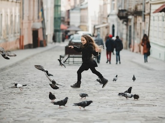 Little girls running with pigeons