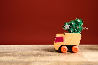 Little toy truck carrying a christmas tree
